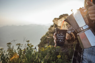 Close-up of woman on a hiking trip at sunrise pouring coffee into a cup - LHPF00074