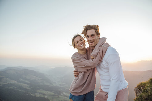 Switzerland, Grosser Mythen, portrait of happy young couple hugging in mountainscape at sunrise - LHPF00080