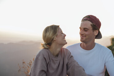 Happy young couple on a hiking trip having a break at sunrise - LHPF00083