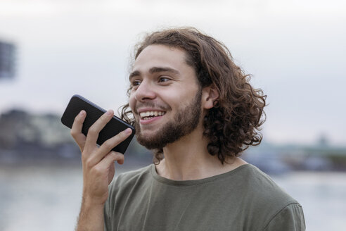 Portrait of happy young man using smartphone outdoors - FMKF05253