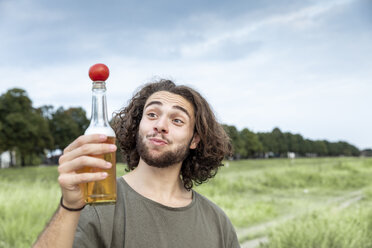 Portrait of smiling young man outdoors balancing tomato on beer bottle - FMKF05280