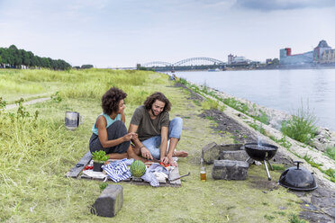 Germany, Cologne, couple having a barbecue at the riverside - FMKF05286