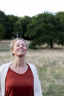 Portrait of happy woman enjoying nature - HHLMF00499