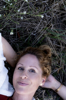 Portrait of smiling woman lying on the ground - HHLMF00502