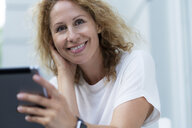 Portrait of smiling woman with tablet - HHLMF00517