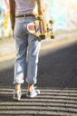Rear view of young woman carrying skateboard in the city - WPEF00781