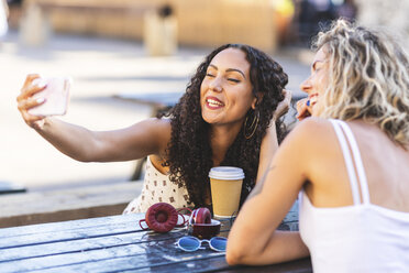 Two happy friends taking a selfie at table outdoors - WPEF00787