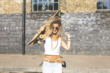 Portrait of smiling young woman carrying skateboard in the city - WPEF00796