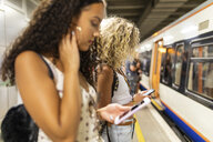 UK, London, two young women with cell phones waiting at underground station platform - WPEF00799