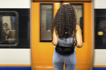 UK, London,  rear view of young woman waiting at underground station platform - WPEF00802