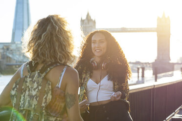 UK, London, two friends together in the city with Tower Bridge in background at sunset - WPEF00808
