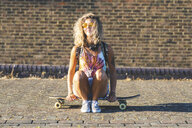 Young woman sitting on a skateboard with brick wall in background - WPEF00811