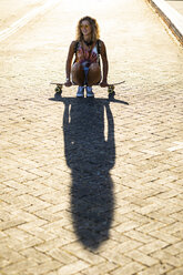 Young woman sitting on a skateboard in sunlight - WPEF00814