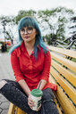 Portrait of young woman with dyed blue hair sitting on a bench with beverage - VPIF00825