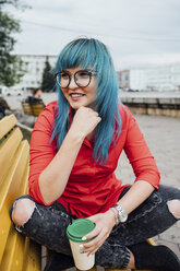Portrait of smiling young woman with dyed blue hair sitting on a bench with beverage - VPIF00831