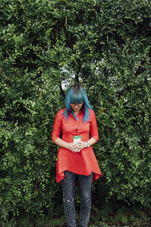 Young woman with dyed blue hair standing in front of a hedge with beverage - VPIF00834