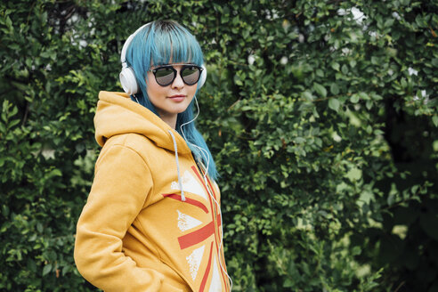 Portrait of young woman with dyed blue hair and headphones wearing yellow hooded jacket - VPIF00837