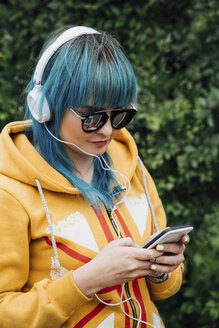 Portrait of young woman with dyed blue hair listening music with headphones looking at smartphone - VPIF00840