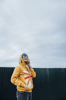 Portrait of young woman with dyed blue hair and headphones wearing fashionable hooded jacket - VPIF00843
