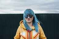 Portrait of young woman with dyed blue hair wearing sunglasses and hooded jacket - VPIF00846