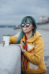 Portrait of young woman with dyed blue hair wearing mirrored sunglasses and fashionable hooded jacket - VPIF00849