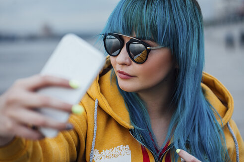 Portrait of young woman with dyed blue hair taking selfie with smartphone - VPIF00852