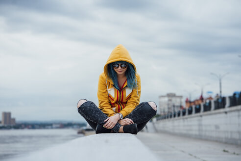 Young woman with dyed blue hair sitting on a wall wearing fashionable hooded jacket - VPIF00855