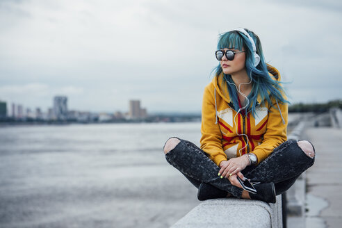 Young woman with dyed blue hair sitting on a wall listening music with headphones and smartphone - VPIF00858