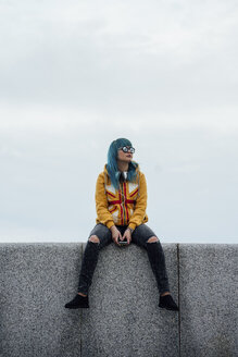 Young woman with dyed blue hair sitting on a wall looking at distance - VPIF00861