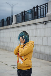 Young woman covering face with her dyed blue hair - VPIF00867