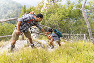 Italy, Massa, man helping a young woman to climb a step while hiking in the Alpi Apuane mountains - WPEF00851