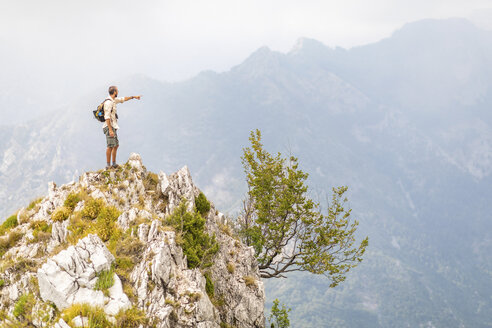 Italy, Massa, man standing on top of a peak in the Alpi Apuane mountains - WPEF00854