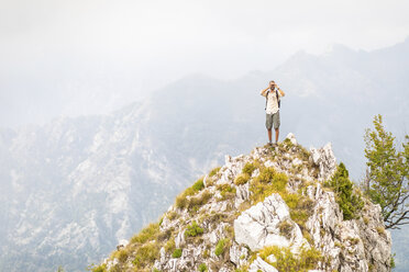 Italy, Massa, man standing on top of a peak in the Alpi Apuane mountains - WPEF00857