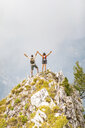 Italy, Massa, happy couple cheering on top of a peak in the Alpi Apuane mountains - WPEF00860