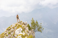 Italy, Massa, young woman standing on top of a peak in the Alpi Apuane mountains - WPEF00863