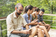 Italy, Massa, hikers in the Alpi Apuane mountains looking at their smartphones and sitting on a bench - WPEF00884