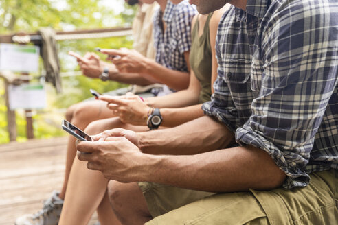 Italy, Massa, hikers in the Alpi Apuane mountains looking at their smartphones and sitting on a bench - WPEF00887