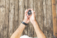 Close-up of man on boardwalk holding a compass - WPEF00890