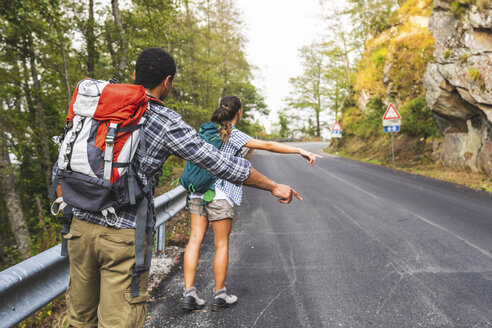Italy, Massa, couple hitchhiking on a road in the Alpi Apuane mountains - WPEF00914