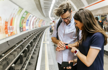 UK, London, couple waiting at   underground station platform looking at smartwatch - MGOF03790