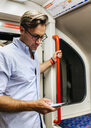 UK, London, businessman in underground train looking at cell phone - MGOF03793