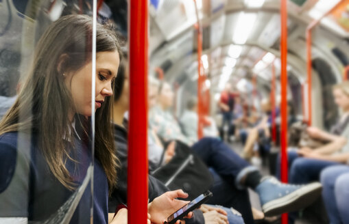 UK, London, young woman in underground train looking at cell phone - MGOF03796