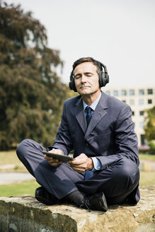 Businessman in city park wearing headphones and holding tablet - MOEF01380