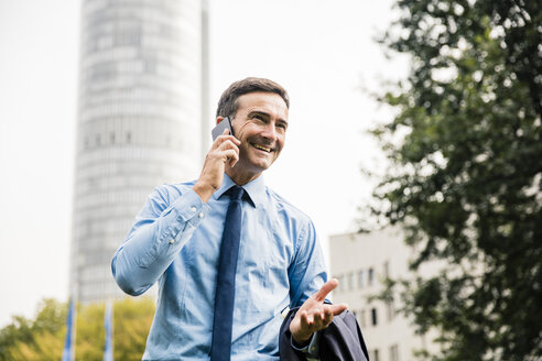 Smiling businessman on cell phone in city park - MOEF01389