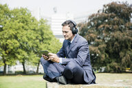 Businessman in city park wearing headphones and using tablet - MOEF01395