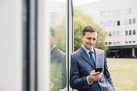 Smiling businessman using cell phone leaning against glass front - MOEF01410