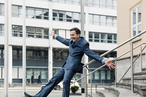 Carefree businessman sliding down railing in the city - MOEF01413