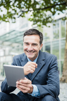 Portrait of smiling businessman with tablet in the city - MOEF01419