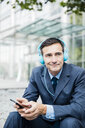 Smiling businessman listening to music with headphones in the city - MOEF01422