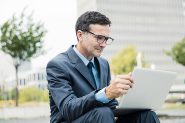 Businessman sitting down using laptop in the city - MOEF01434